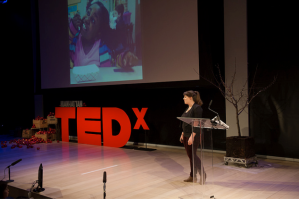 Photo 1. Sunny Young at TEDxManhttan on March 2014. Slide showing second grade student, Samaria, eating kale chips after meeting the farmer who grew the kale and the chef who prepared them. TEDxManhattan.